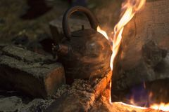 The kettle is heated on a fire at night outdoor. The kettle is heated on a bright fire at night outdoor stock image