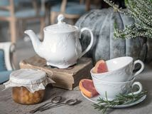 Kettle, jam, old book and wo tea cups with rosemary and grapefruit on the background of a large pumpkin and heather. Tea. Autumn stock images