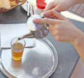 A kettle of moroccan mint tea and a glass. A person is pouring moroccan mint tea into a glass Royalty Free Stock Image