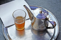 A kettle of moroccan tea and a glass Stock Image