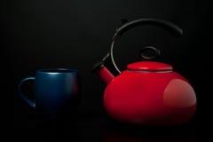 Kettle and Mug. Red tea kettle and blue mug against black background Stock Photos