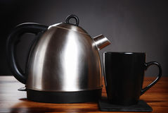 Kettle and mug. A modern kettle and mug on a wooden table in front of a dark background royalty free stock photos