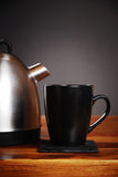 Kettle and mug. A modern kettle and mug on a wooden table in front of a dark background stock photography