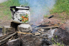 Kettle over burning campfire. Kettle over the burning campfire royalty free stock photography