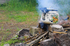 Kettle over burning campfire Stock Images