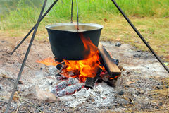 Kettle over campfire Stock Images