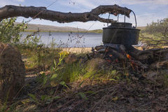 Kettle over campfire. Coffee kettle over bonfire with lake in background Stock Photo