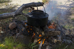 Kettle over campfire. Coffee kettle over burning campfire Royalty Free Stock Image