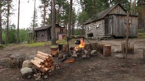 Kettle over campfire near hut in forest stock video footage
