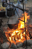 Kettle and pot on the fire. In the campaign Royalty Free Stock Images