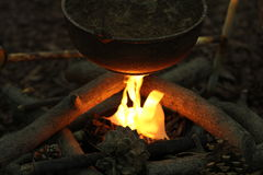 A kettle pot over a campfire. A kettle pot over a campfire with wood, pine cones and a flame stock photos