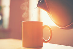 Kettle pouring boiling water into cup Royalty Free Stock Photos