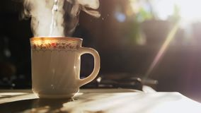Kettle pouring boiling water into a cup. Slowmotion. Kettle pouring boiling water into a cup during breakfast in morning sunlight in slowmotion. Sunlight and stock video footage