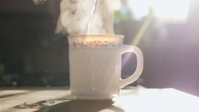 Kettle pouring boiling water into a cup. Slowmotion. Slow Motion: Kettle pouring boiling water into a cup during breakfast in morning sunlight in slowmotion stock video
