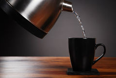 Kettle pouring into mug Royalty Free Stock Photos