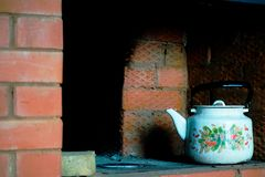 Kettle in the Russian old red brick oven. Symbol of a hearth and home Stock Photo