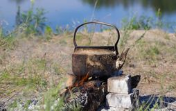 Kettle  in soot hung over the fire in the campfire on fire Royalty Free Stock Image