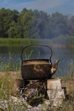 Kettle  in soot hung over the fire  on nature Stock Images