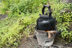 Kettle and soot on stove. Burn firewood royalty free stock image