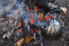 Kettle stands by the fire on the lake stock photos