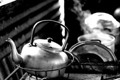 Kettle In A Thai Kitchen. Black and white portrait of a kettle amidst other cookware in a Thai kitchen.  Focus on kettle Royalty Free Stock Images