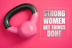 Kettle Weights on Pink Background with Inspirational Quote. Strong Women Get Things Done. Strong women get things done. Inspirational quote with women`s kettle Royalty Free Stock Photography
