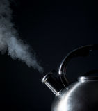 Kettle whistling, boiling kettle, steam,  on a black Royalty Free Stock Photography