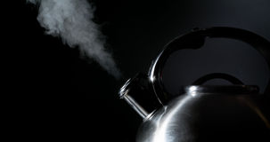 Kettle whistling, boiling kettle, steam,  on a black Royalty Free Stock Image