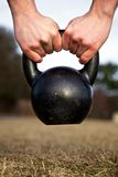 Kettlebell. Closeup of hands lifting kettlebell Royalty Free Stock Photography