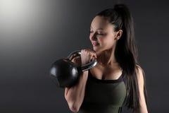 Закройте вверх женской модели фитнеса держа kettlebell в положении шкафа Стоковые Фото