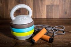 可调整的kettlebell和跳绳在木背景 健身训练的重量 库存图片