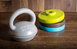 在木背景的可调整的kettlebell 健身训练的重量 免版税图库摄影