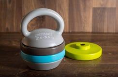 在木背景的可调整的kettlebell 健身训练的重量 库存照片