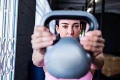 Kettlebell de levage sérieux d'athlète féminin dans le gymnase photos stock