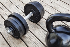 Kettlebell and dumbbell. Exercise weights - kettlebell and dumbbells on a wooden deck - a home gym concept Stock Photos