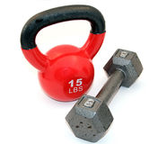 Kettlebell and dumbbell. A fifteen pound kettlebell and eight pound dumbbell over white royalty free stock images