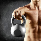 Kettlebell dumbbell - fitness man lifting weight. Kettle bell training crossfit. Muscular shirtless male torso close up on blackboard background Stock Image