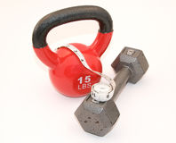 Kettlebell and dumbbell and measuring tape. A kettlebell and dumbbell and measuring tape over white Stock Photography