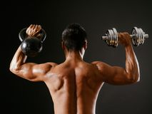Kettlebell or dumbbell. Photo of an Asian male exercising with both a kettlebell and a dumbbell, doing shoulder press over dark background Royalty Free Stock Photo