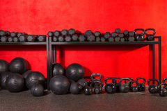 Kettlebell  dumbbell and weighted balls at gym. Kettlebell dumbbell and weighted slam balls weight training equipment at gym red walls Stock Images
