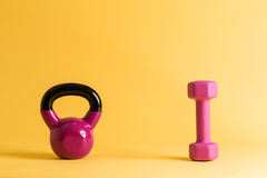 Kettlebell and dumbbell. On a yellow background Stock Photo