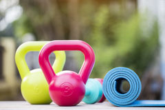 Kettlebell, dumbbell and yoga mat. On wood table Stock Image