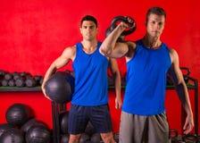 Kettlebell et hommes pesés de gymnase de séance d'entraînement de boule Photographie stock libre de droits