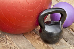 Kettlebell and exercise balls. Black iron kettlebell, Swiss and medicine exercise balls on wooden deck - fitness concept Royalty Free Stock Image
