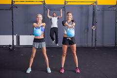 Kettlebell fitness training woman and man doing pull up. Kettlebell fitness training women in a gym stock image