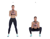 Kettlebell goblet squat. Athletic woman performing a functional exercise with kettlebell stock image