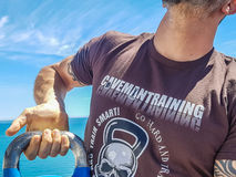 Kettlebell Hook Grip. Taco Fleur from Cavemantraining demonstrates the kettlebell hook grip. Background shows the Mediterranean sea on the Costa del Sol Stock Image