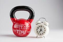 Kettlebell rouge avec le lettrage de temps de séance d'entraînement et l'alarme traditionnelle Photographie stock