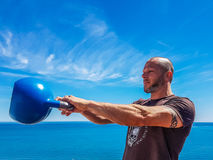Kettlebell Swing. Taco Fleur from Cavemantraining performing the conventional kettlebell swing with two arms. Background shows the Mediterranean sea on the Costa Stock Photography