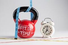 Kettlebell vermelho com rotulação do tempo do exercício, cl tradicional do alarme Fotografia de Stock